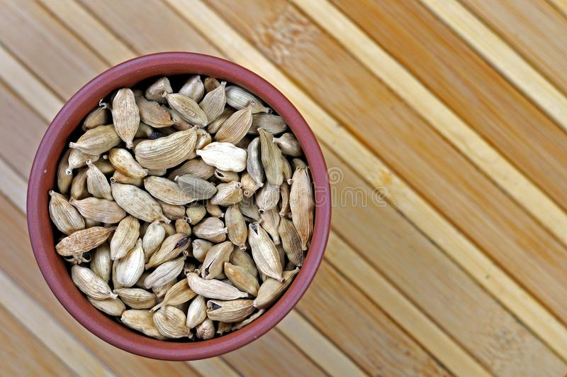 De capsules van het kardemomzaad in aardewerkkom stock foto