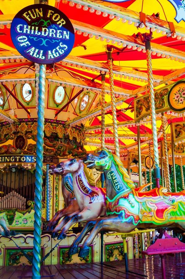 De carrousel met paarden op Vrolijk Carnaval gaat rond royalty-vrije stock afbeeldingen