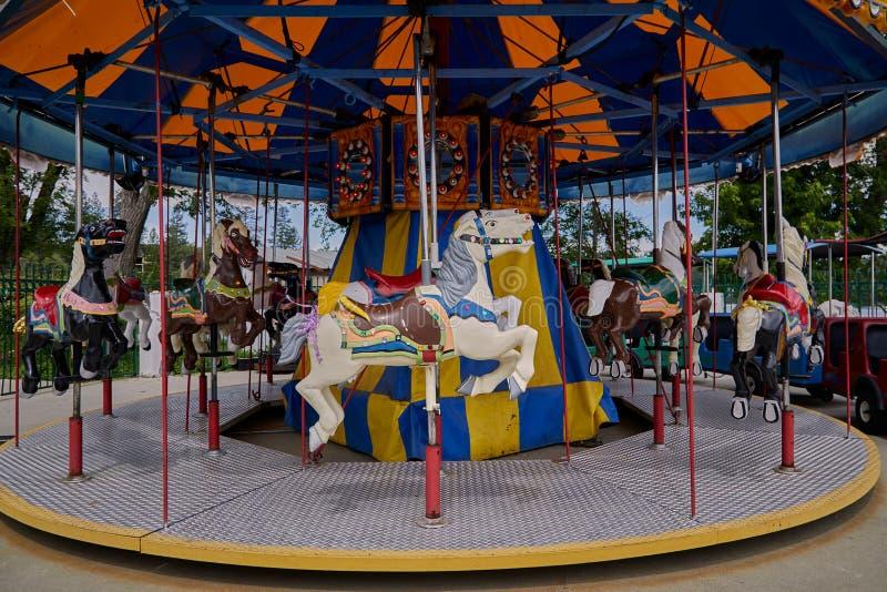 De carrouselpaarden op Vrolijk gaan rond stock foto's