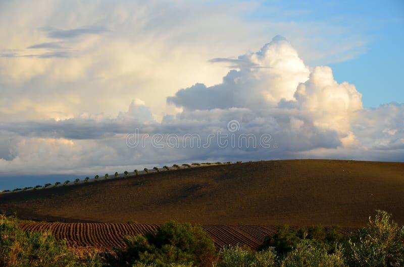 De wolken van de regen boven de vruchtbare heuvels stock afbeeldingen