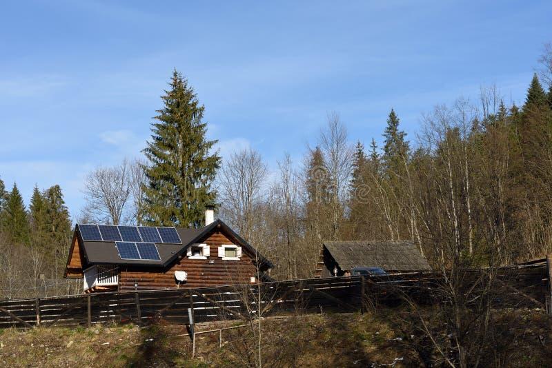 De cellen van moduleszonnepanelen op houten plattelandshuisje stock afbeeldingen