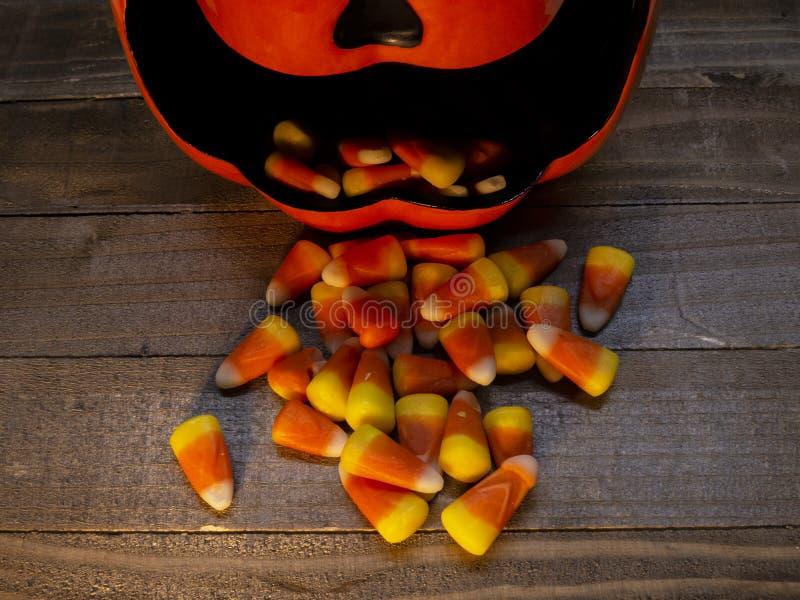 De ceramische schotel van het pompoensuikergoed met suikergoedgraan die uit de mond morsen stock afbeelding