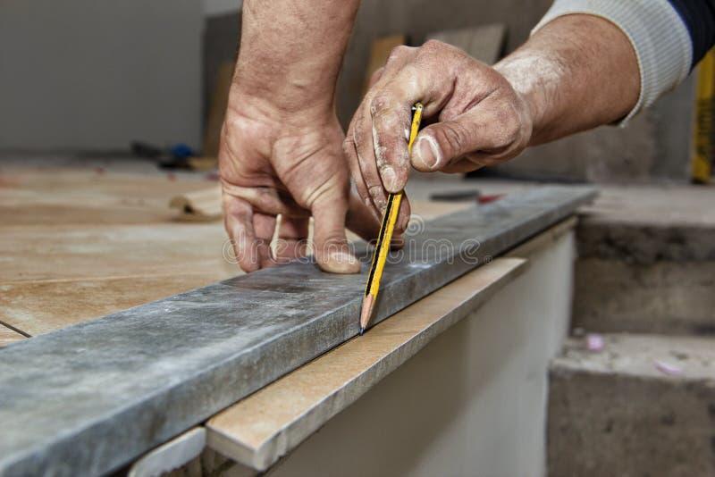 De ceramische vloer betegelt - mensenhanden merkend te snijden tegel, close-up royalty-vrije stock afbeelding