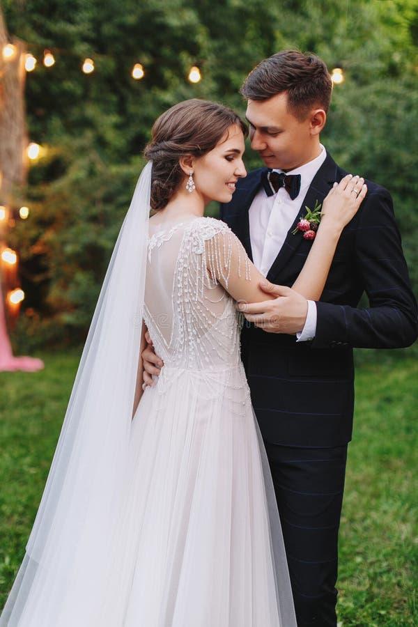 De ceremonie van het avondhuwelijk met lantaarns en lampen op boom Bruid en bruidegom die op achtergrond van bollichten koesteren stock foto's