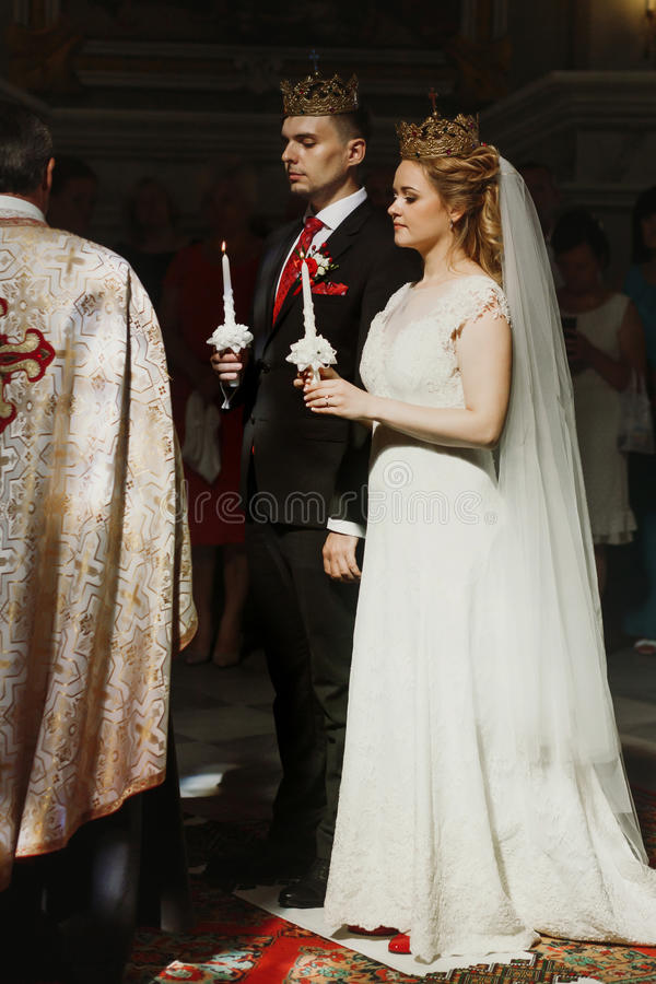 De Ceremonie van het huwelijk bij Kerk modieuze bruidegom en bruidholding cand stock foto