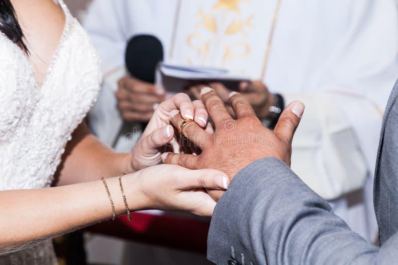 De ceremonie van het huwelijk De bruid zet de verlovingsring op de bruidegom De dag van het huwelijk stock foto's