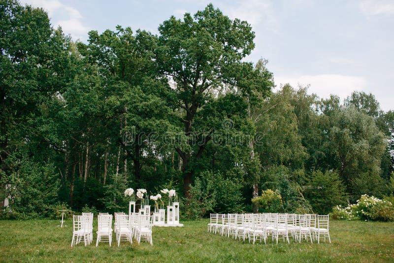 De ceremonie van het huwelijk in een mooie tuin witte stoelen en weerspiegelde lijsten Glasvaas met bloemencalla leliesamaryllis stock foto's