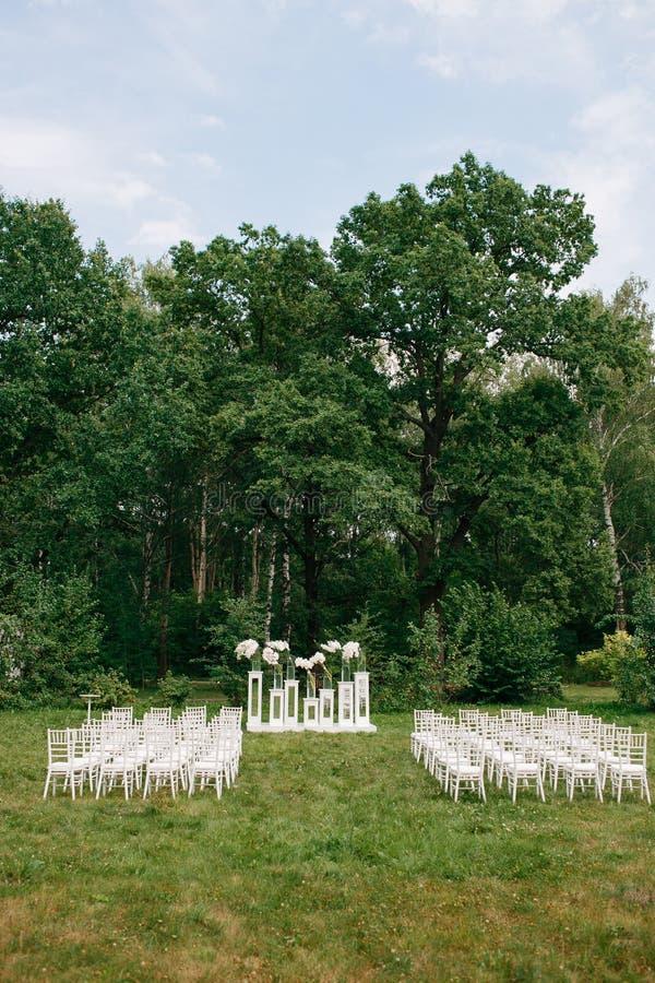 De ceremonie van het huwelijk in een mooie tuin witte stoelen en weerspiegelde lijsten Glasvaas met bloemencalla leliesamaryllis stock afbeeldingen