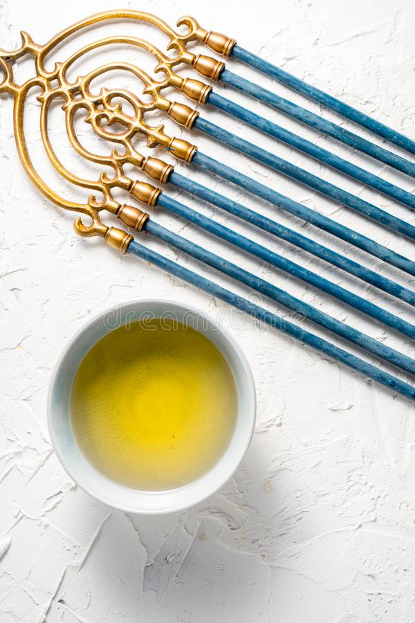 De Chanoeka van het Menorahmessing met blauwe kaarsen en boter in kom hoogste mening stock foto's