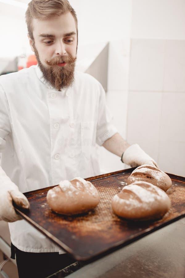 De charismatische bakker houdt het bakseldienblad met onlangs-gebakken brood in de bakkerij royalty-vrije stock foto's