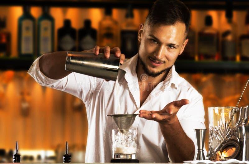 De charmante barman bereidt een heerlijke cocktail voor zijn gast voor stock fotografie