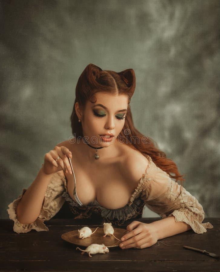De charmante die roodharigedame met kattenoren van haar worden gemaakt eet witte muizen van gouden schotels De gravin pussycat ee stock foto