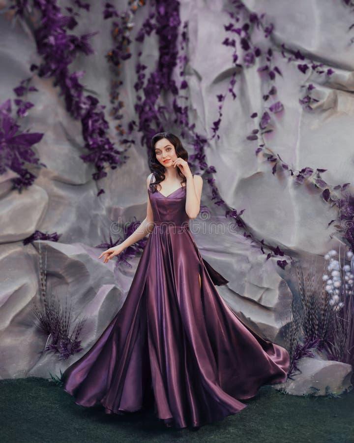 De charmante fee van bloemen en flora bevindt zich dichtbij steenmuur speels stelt voor de camera in lange magische elegant stock afbeeldingen