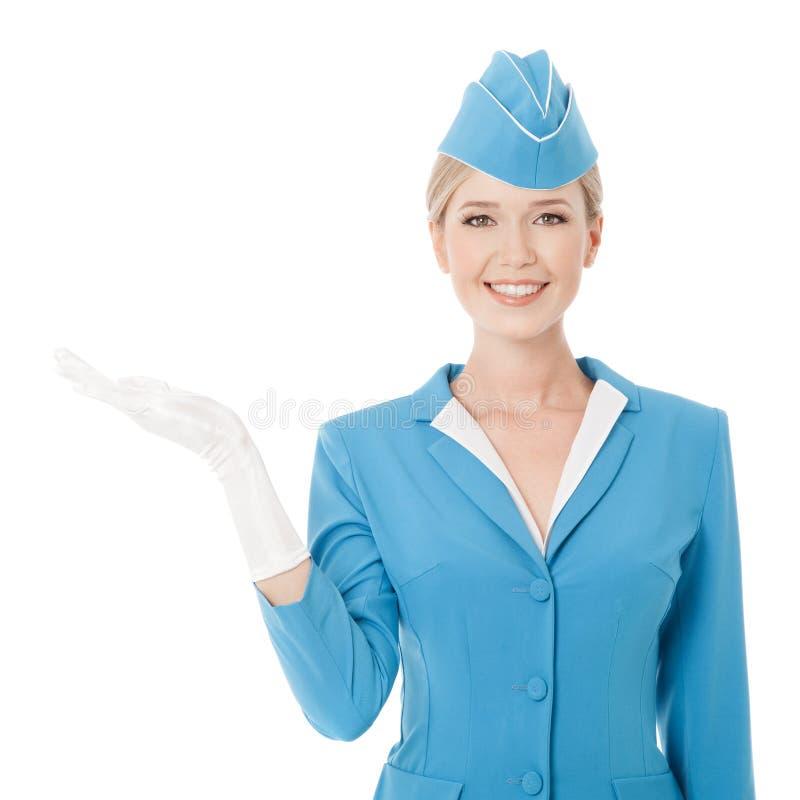 De charmante Holding van Stewardessin blue uniform ter beschikking op W stock fotografie