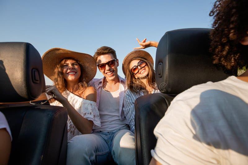 De charmante jonge donkerharigen in hoeden zitten met de jonge mens in zwarte cabriolet en glimlachen op een de zomerdag royalty-vrije stock foto