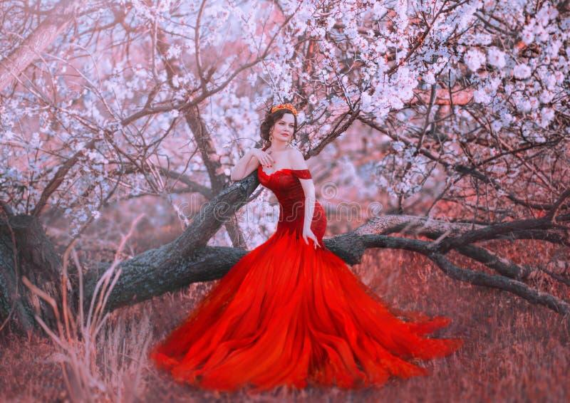 De charmante nimf zit op gevallen boom in de lentebos, dame in schitterende rode scharlaken lange kleding met naakte schouders stock foto's