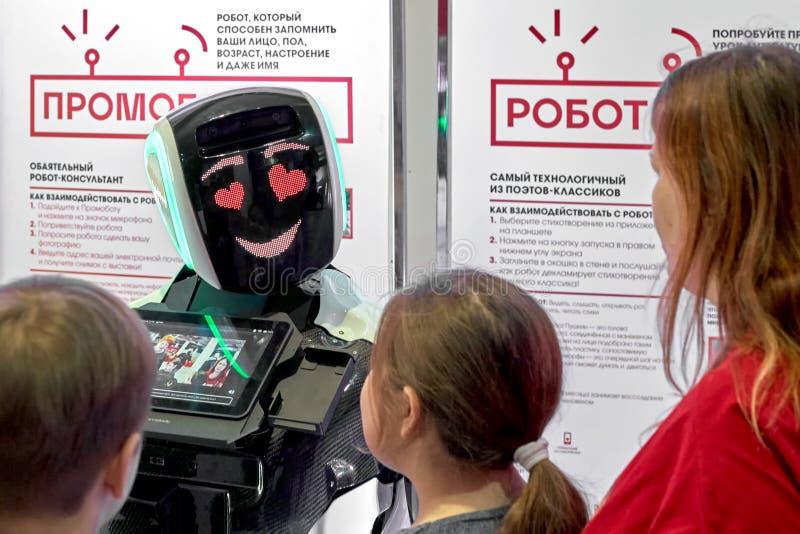De charmante promotorrobot communiceert met bezoekers stock foto