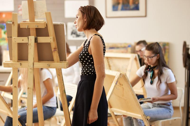 De charmante tekeningsleraar in de mooie kleding toont tekeningstechniek bij de schildersezel in de kunststudio stock foto