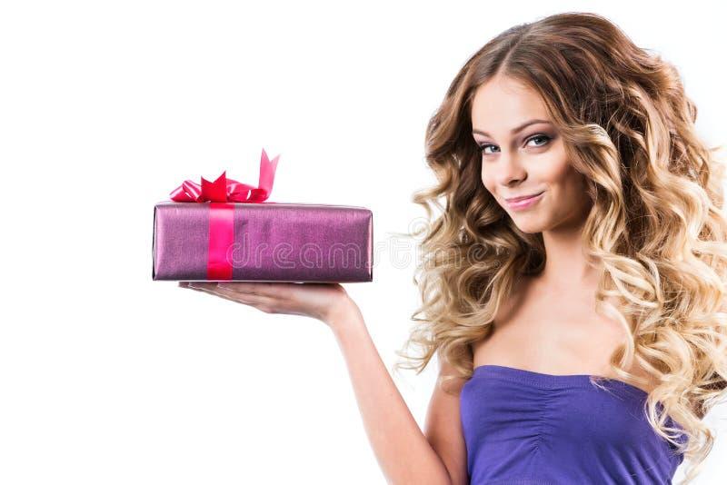 De charmante vrouw met lang krullend haar houdt een gift op een witte achtergrond stock fotografie