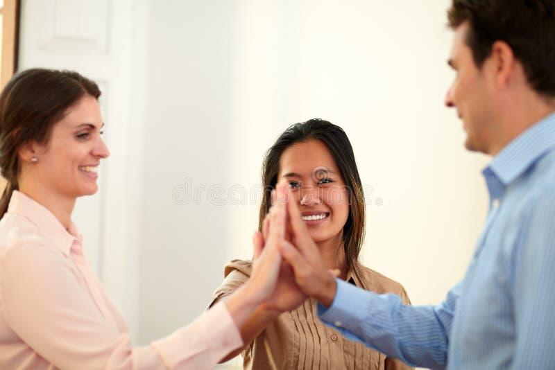 De charmante wirwar van het medewerkersteam hun handen stock afbeeldingen