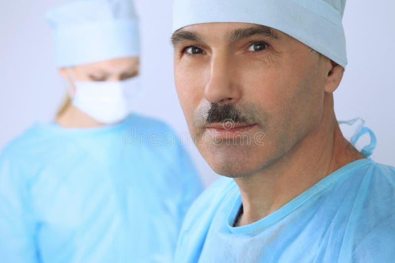 De chef- chirurg onderzoekt de verrichting terwijl het medische team van patiënt bezig is Geneeskunde, gezondheidszorg en noodsit royalty-vrije stock afbeeldingen