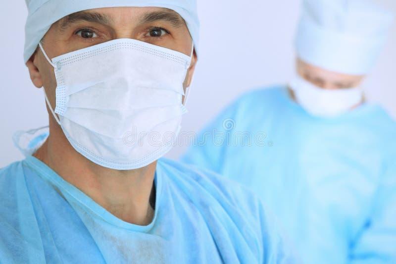De chef- chirurg onderzoekt de verrichting terwijl het medische team van patiënt bezig is Geneeskunde, gezondheidszorg en noodsit stock foto's
