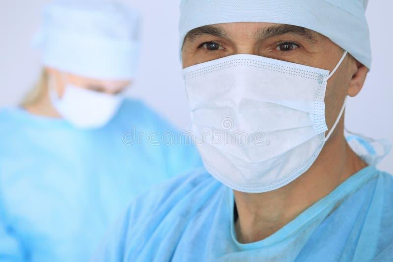 De chef- chirurg onderzoekt de verrichting terwijl het medische team van patiënt bezig is Geneeskunde, gezondheidszorg en noodsit royalty-vrije stock foto's