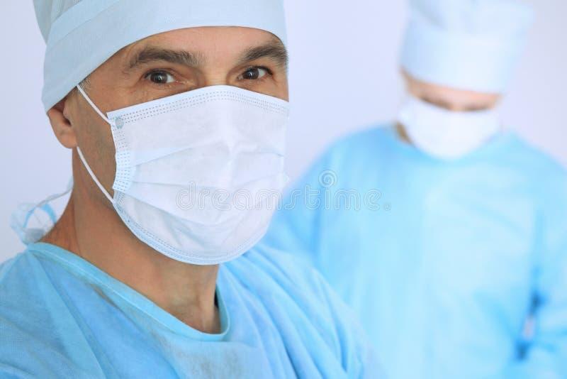 De chef- chirurg onderzoekt de verrichting terwijl het medische team van patiënt bezig is Geneeskunde, gezondheidszorg en noodsit royalty-vrije stock afbeelding