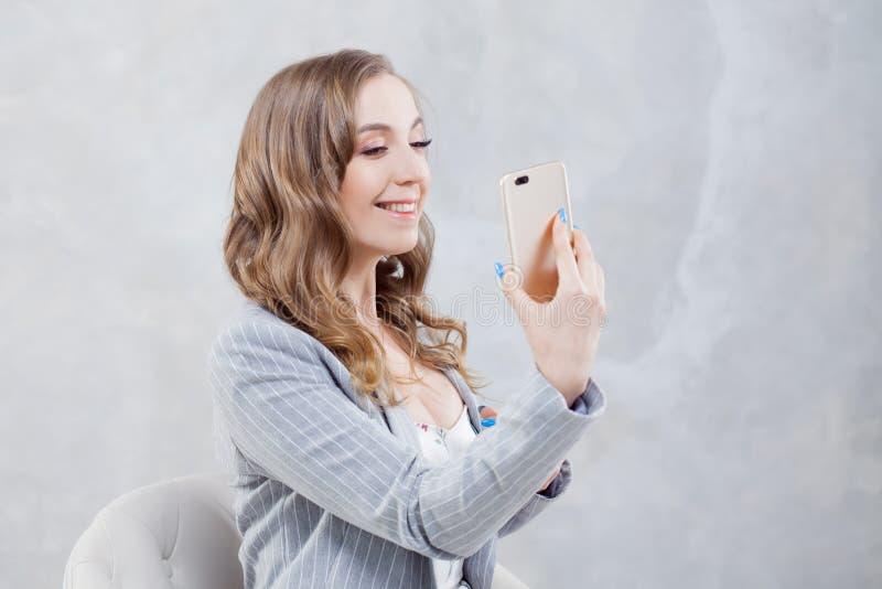 De chef- dame gebruikt een smartphone aan videogesprek stock afbeelding