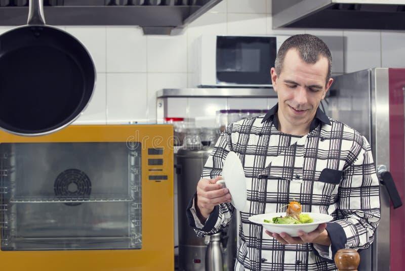 De chef-kok bereidt een maaltijd voor stock afbeeldingen