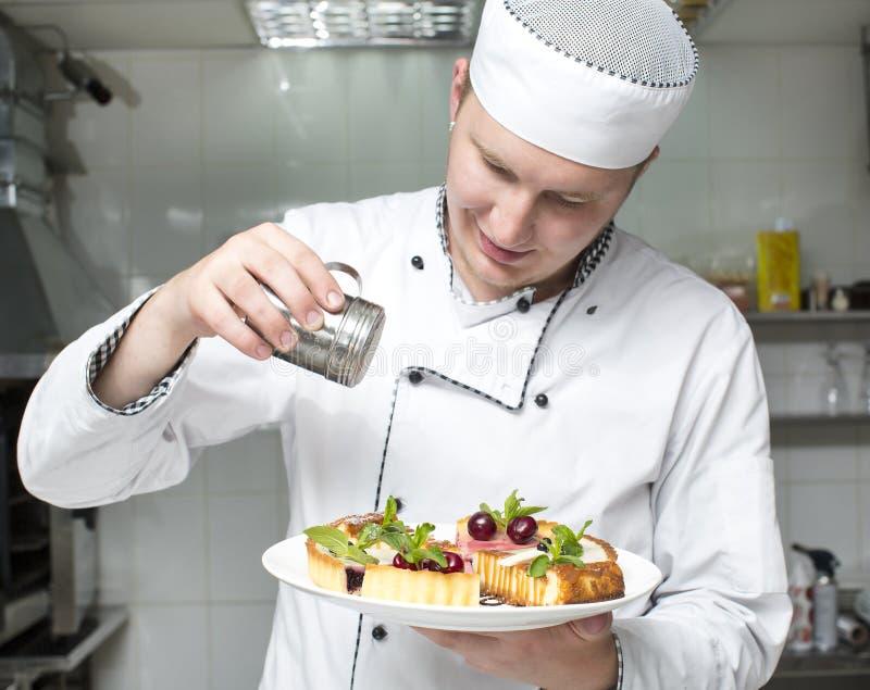 De chef-kok bereidt een maaltijd voor stock foto