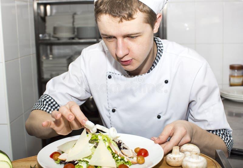 De chef-kok bereidt een maaltijd voor royalty-vrije stock afbeelding