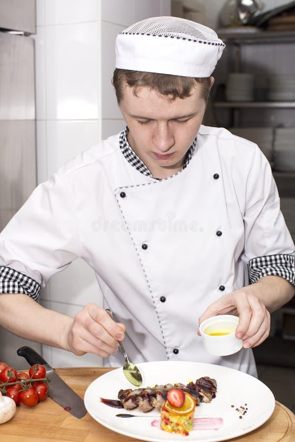 De chef-kok bereidt een maaltijd voor royalty-vrije stock afbeeldingen