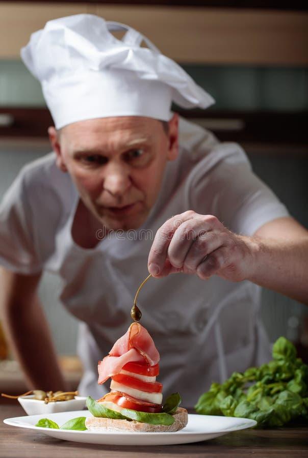 De chef-kok bereidt een snack met mozarella en gerookt vlees voor royalty-vrije stock foto's
