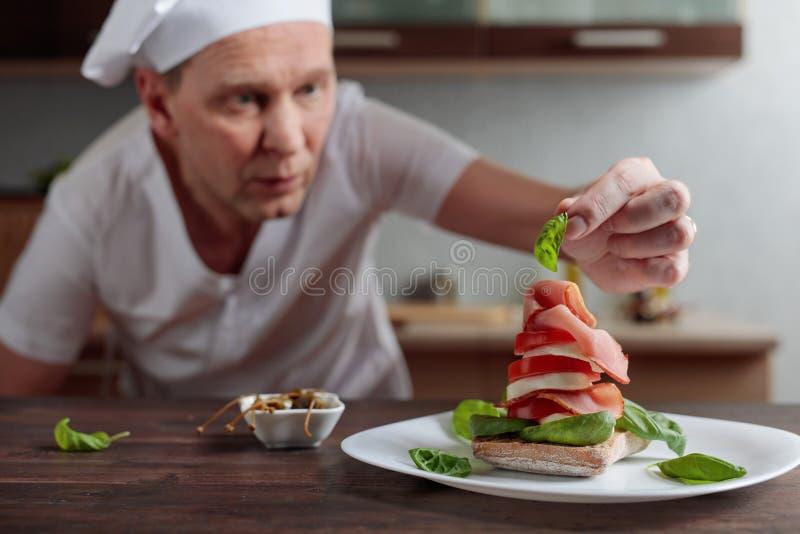 De chef-kok bereidt een snack met mozarella en gerookt vlees voor royalty-vrije stock fotografie