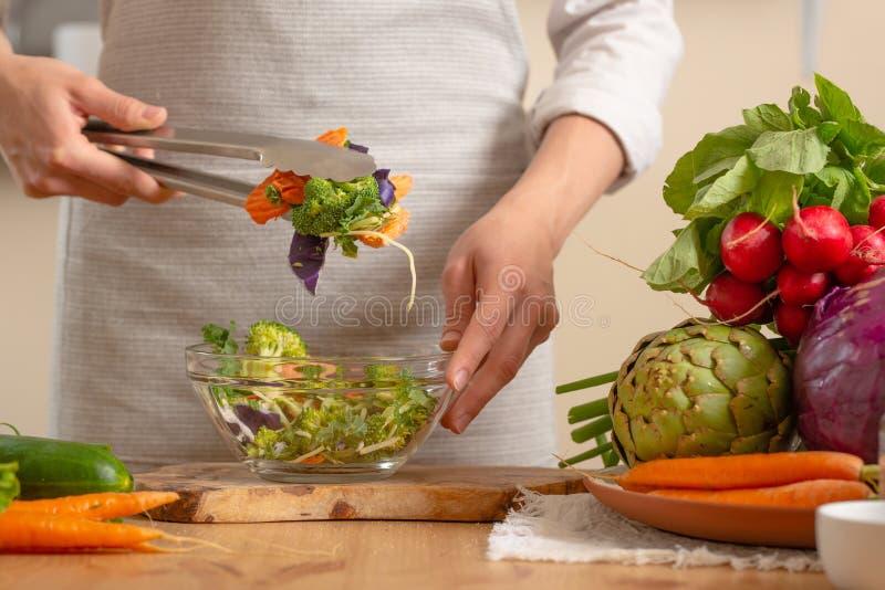 De chef-kok bereidt een vers en helder saladeclose-up, op een lichte achtergrond voor Het concept het verliezen van gezond en gez royalty-vrije stock afbeelding