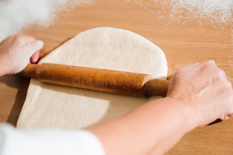 De chef-kok bereidt het deeg voor - het proces om deeg in de keuken te maken stock foto's