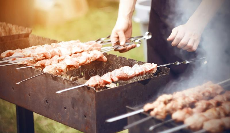 De chef-kok bereidt kebabs op de grill in de zomer voor royalty-vrije stock foto