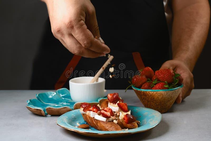 De chef-kok bestrooit de noten zoete sandwiches met aardbeien, kaas, camembert, Brie, noten en honing op het gehele korrelbrood b stock afbeeldingen