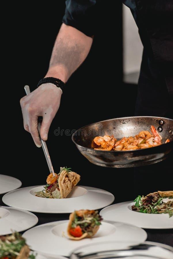 De chef-kok bij het restaurant die Kruidige Garnalentaco's met Koolsla en Salsa maken stock fotografie