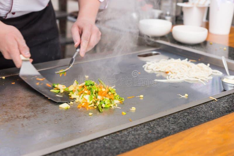 De chef-kok die groente voorbereiden beweegt gebraden gerecht over een warmhoudplaat stock fotografie
