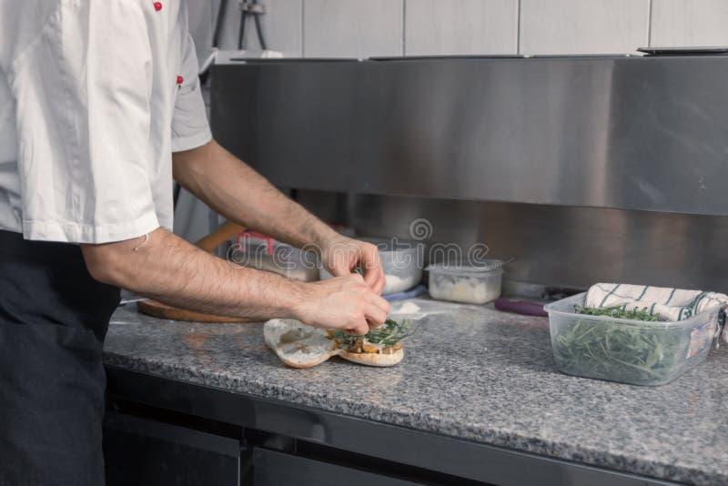 De chef-kok die van close-uphanden sandwich voorbereiden stock afbeeldingen