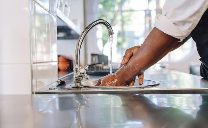 De chef-kok die van hem wassen dient commerciële keuken in royalty-vrije stock afbeelding