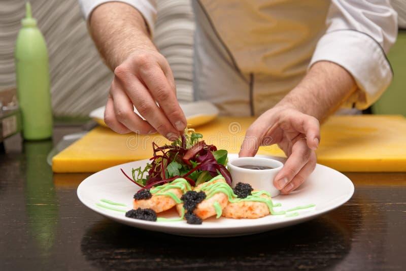 De chef-kok dient krabcakes met salademengeling, jus, zeewierkaviaar royalty-vrije stock afbeeldingen