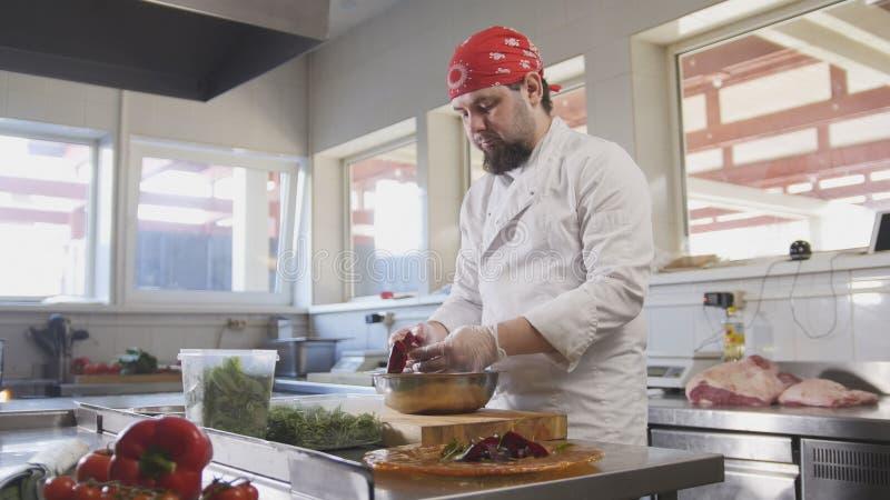 De chef-kok dient de salade door de ingrediënten op een plaat te plaatsen stock afbeelding