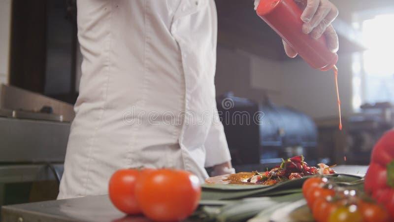 De chef-kok dient de salade toevoegend de saus, verse groenten in de voorgrond stock afbeelding