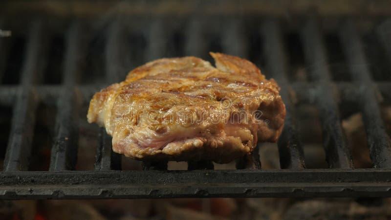De chef-kok draait een groot sappig en dik stuk van rundvlees, lams of varkensvleesvlees op de grill met de tang, en toen scherp royalty-vrije stock foto's