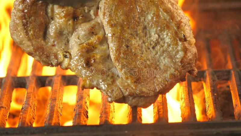 De chef-kok draait het varkensvleeslapje vlees op de grill met tang en bekijkt hoeveel het gebraden was royalty-vrije stock foto
