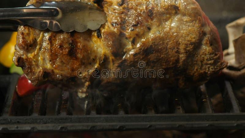 De chef-kok draait lapje vlees met tang, langzame motie van lapje vlees, die lapje vlees met geroosterde groenten koken stock foto