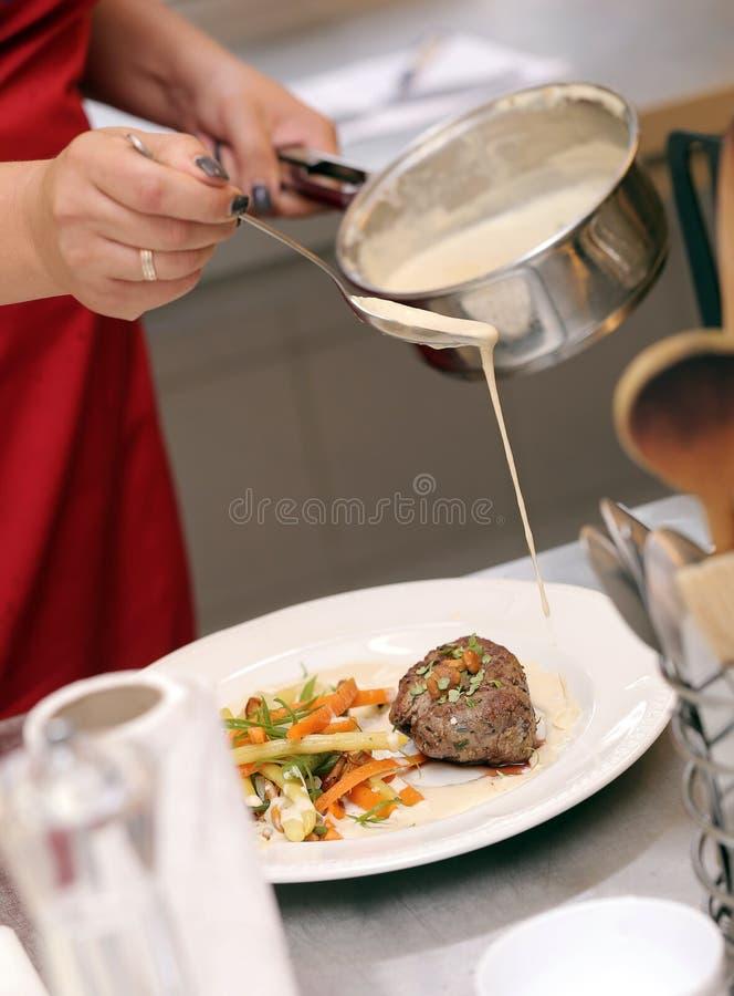 De chef-kok giet wat saus in de schotel royalty-vrije stock foto